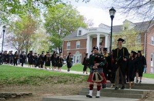 The Class of 2015, making their way across campus to the Commencment tents led by bagpipe player.